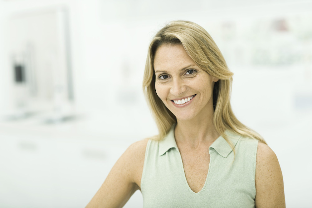 middle aged white woman smiling with bright white teeth